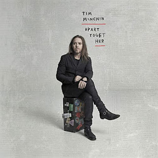 Tim Minchin sitting on a suitcase covered in travel stickers. Hand written album title