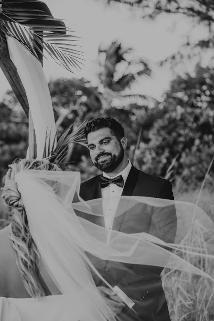 Candid photography of groom during outdoor ceremony.