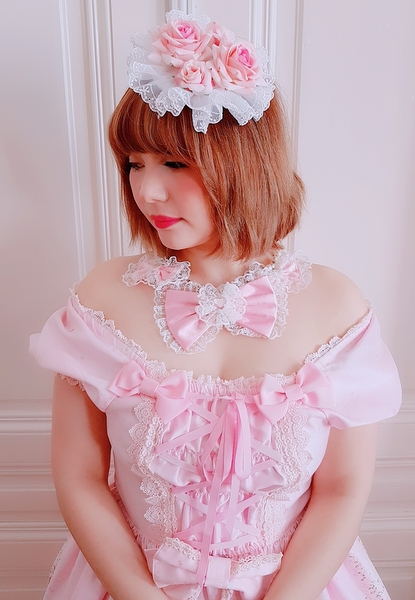 auris with a rose headdress, a pink dress and a pink ribbon necklace