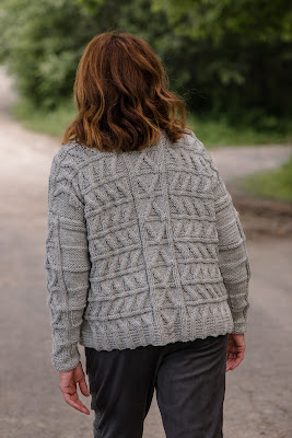 Photo of model wearing hand knitted cable sweater and walking away from the camera