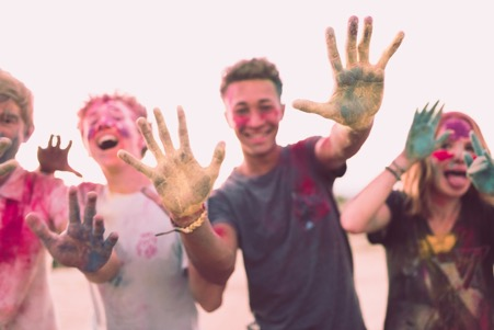 happy teenagers covered in coloured substance