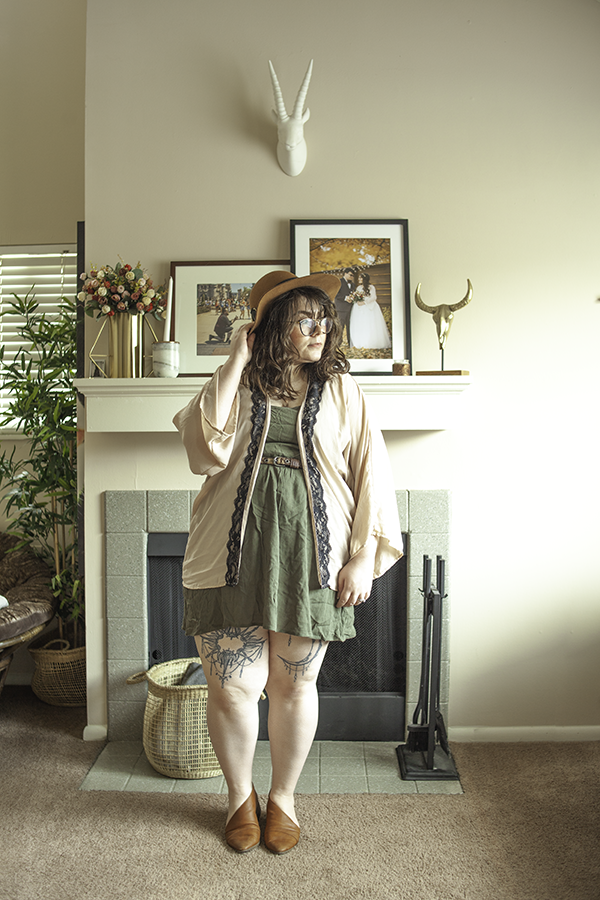 "An outfit consisting of a brown panama hat, dusty pink ""kimono"" with black lace trim, olive green mini dress, and brown d'orsay flats."