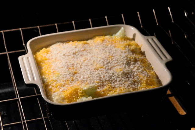The cauliflower gratin being added to the oven.