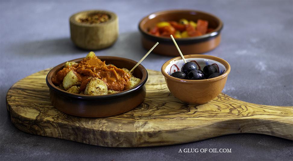 patatas bravas and tapas on an olive wood board