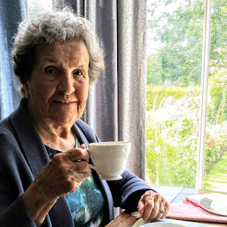 An image of an elderly lady holding a cup of tea in a white china cup. She is seated by a window with a blurry view of an English garden. The lady is wearing shades of blue and is looking warmly at the photographer