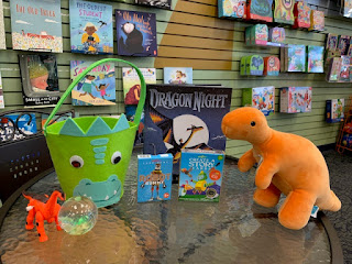 a green felt bucket with a dinosaur face sits next to a ball, a small toy dragon, a book about a dragon, and an orange plush dinosaur