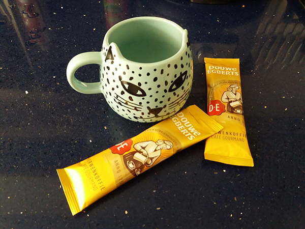 A cat-shaped cup and two coffee sachets on a kitchen counter