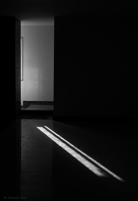 A Black and White Minimal Art Photo of Light Rays coming through a Window, lightning a Dark Isolated Hall of a Building in Jaipur.