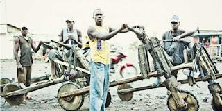 grupo de quatro rapazes com scooters em madeira no Congo