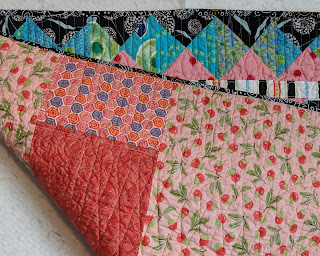 Folded quilt shows part of the border and the peach fabrics making the back of the Hourglass quilt.
