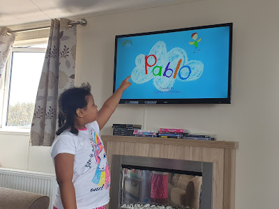 Sparkle, a little mixed-race girl, pointing at Pablo playing on a TV screen..