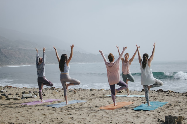 4 ladies with a yoga instructor doing yoga at the coast of the sea.