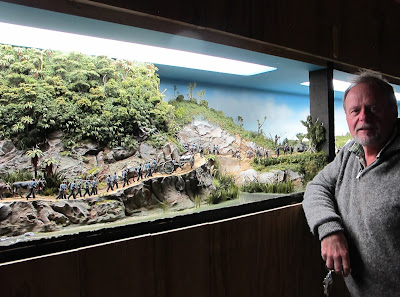 A man poses in front of a diorama of 19th-century soldiers marching in the New Zealand bush.