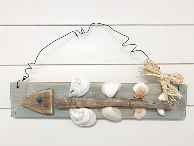 fish bone art hanging on a shiplap wall