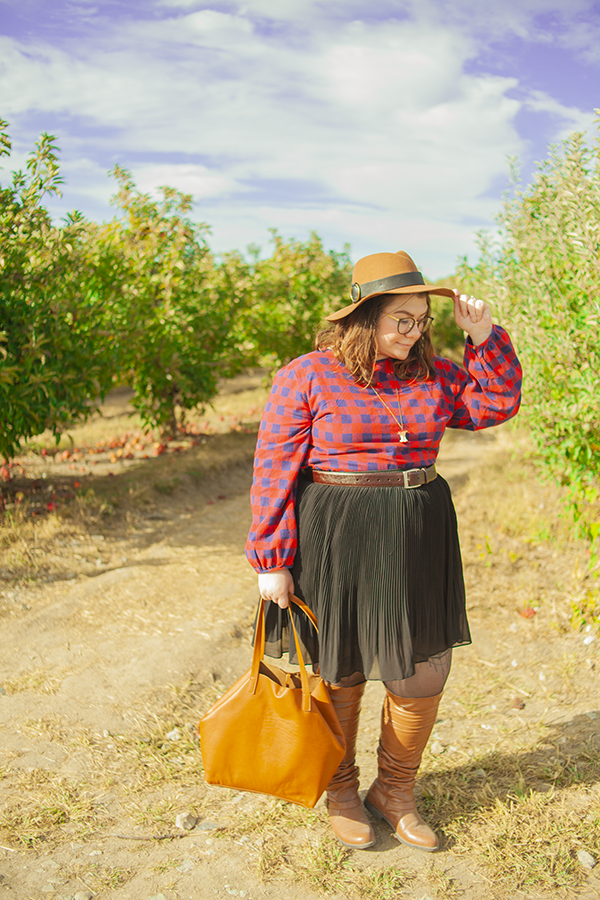 An outfit consisting of a brown panama hat, red and navy blue buffalo plaid blouse tucked into a black pleated knee length skirt and brown knee boots.
