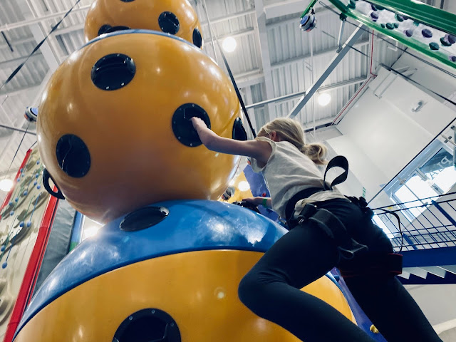 A climbing wall that looks like large balls balanced on top of each other and an 8 year old girl climbing up it
