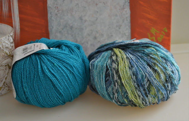 Superwash wool and silk blend lace weight yarn in turquoise and shades of blue and green self striping.