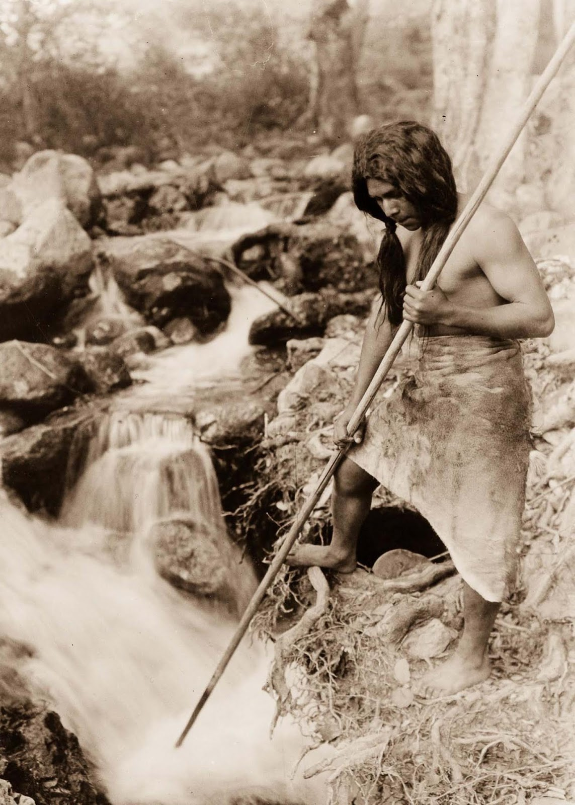 A Hupa spear fisherman watches for salmon. 1923.