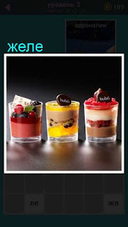 на столе стоят три стакана в которых слоями лежит желе разного цвета