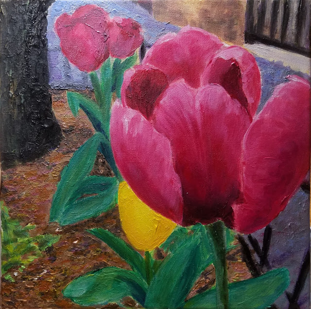 spring tulips and a tree trunk in a sidewalk-planter
