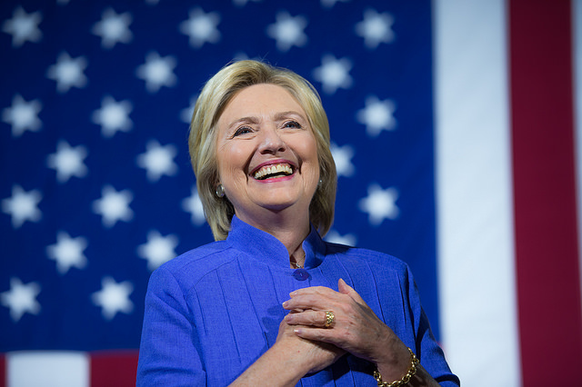image of Hillary clasping her hands to her heart and smiling broadly while standing in front of a US flag