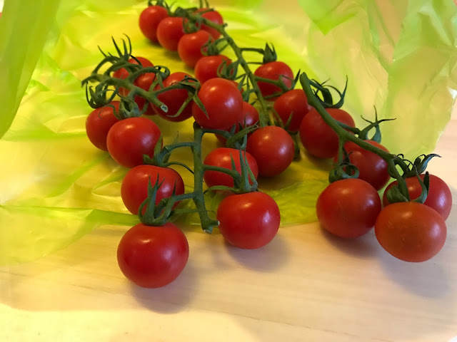 Cherry tomatoes on the vine shown half in a green plstic fresher for longer bag