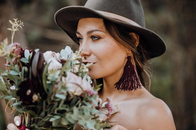 Boho Bride: Panna Młoda w boho stylizacji: zielony kapelusz, burgundowe kolczyki i piękny bukiet.
