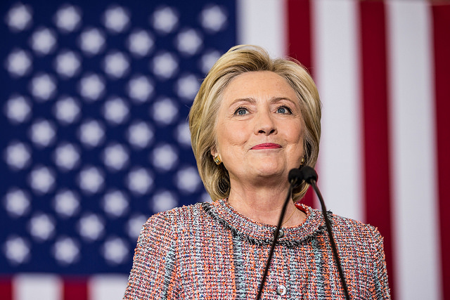 image of Hillary Clinton on the campaign trail, standing in front of a US flag, smiling
