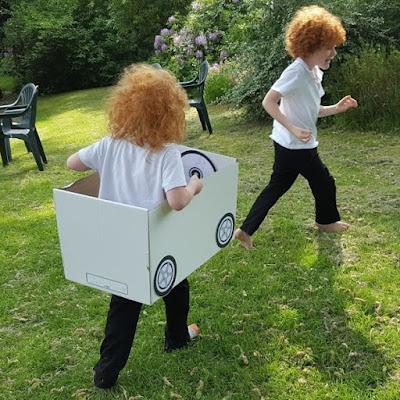 Car Boys playing with cardboard car