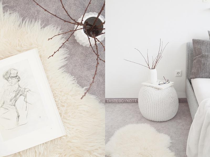 Winterdeko, gemütliches Schlafzimmer mit Fell, Kissen, Zweigen, Strickpouf, Origami-Vase und Kunstbuch in weiß-hellgrau. Tipps: Einrichten mit Teppichböden. Tasteboykott.