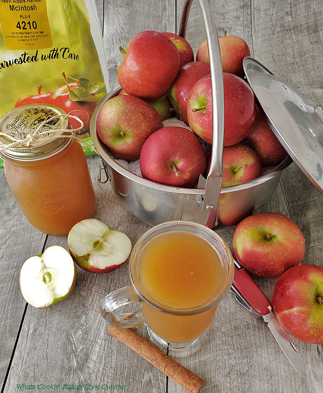 this is a photo of homemade apple-cider in a glass cup with apples in a big pot, mason jar filled with cider and sliced and quartered apples in the photo with a knife to slice them