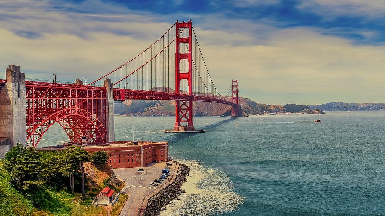 ponte golden gate vermelha com agua do mar azulada, ceu aberto com nuvens. Forte de pedra nos pes da ponte