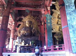 una statua più piccola di Buddha dorato accanto alla statua principale