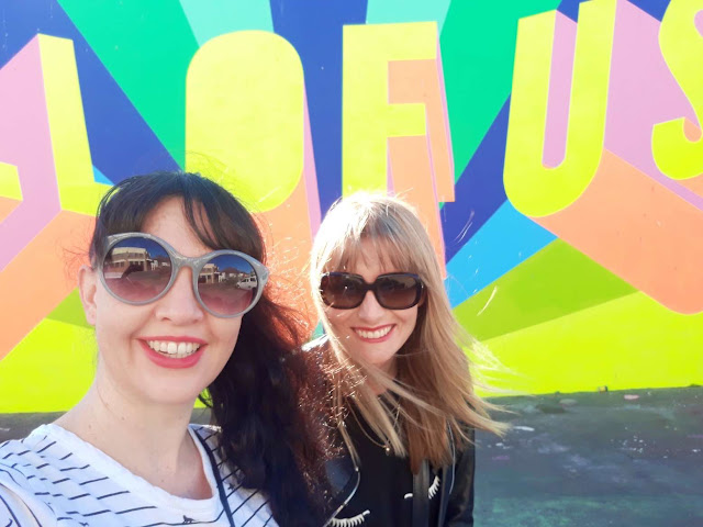 Two people stand in front of 'All of Us' Mural in Woodstock