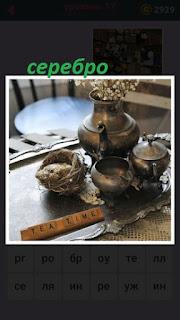на столе на подносе лежит разная посуда из серебра