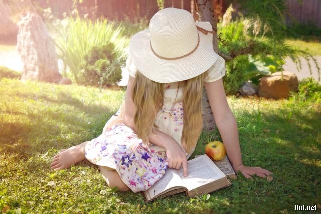 ảnh bé gái dễ thương đang chăm chú đọc sách