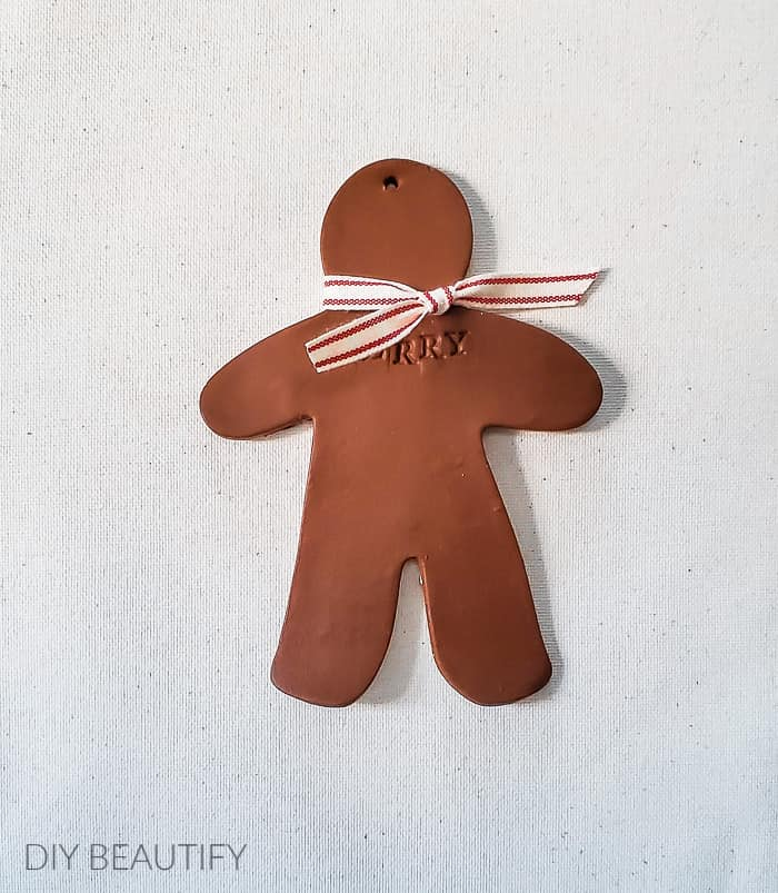 clay gingerbread man with red striped bow