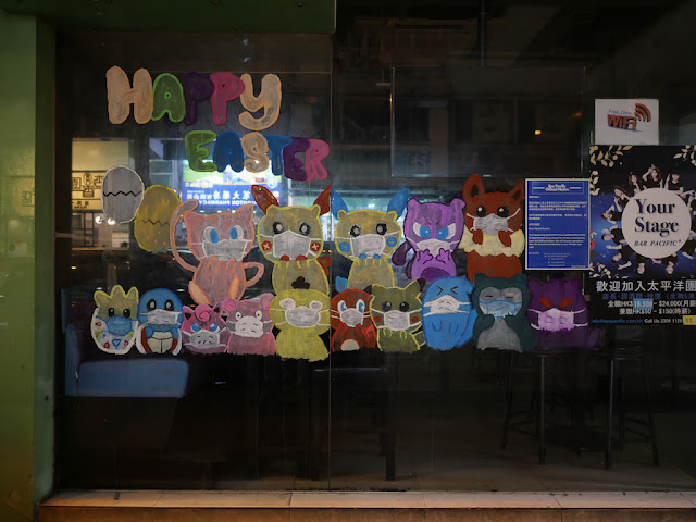 """Happy Easter"" along with numerous animals wearing face masks painted on a window"