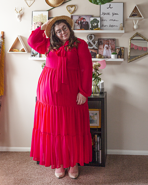 An outfit consisting of a straw boater hat, a red long bishop sleeve tiered maxi dress, and beige heels.