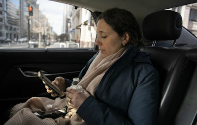Julie Pace using her mobile phone sitting inside her car