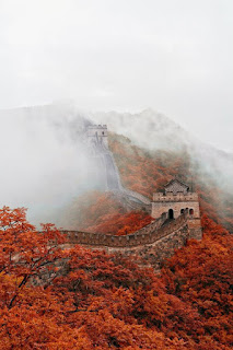 Mist and red foliage around the Great Wall of China.