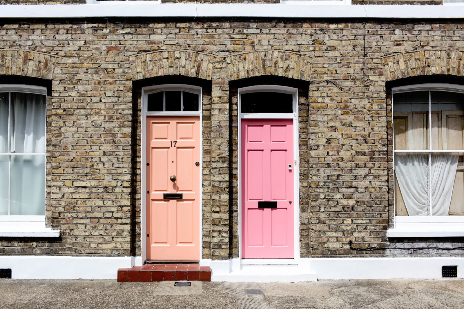 Two front doors in pastel pink in adjoining houses on a terraced street