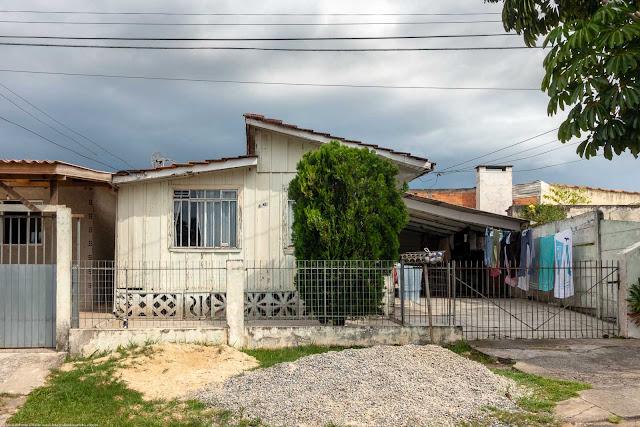 Casa de madeira na Rua Ary Barroso com roupa estendida no varal.