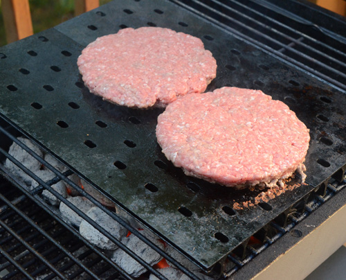 Griddle cooking burgers on the PK Grill