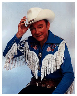 Portrait of Roy Rogers in cowboy costume smiling and tipping his white hat