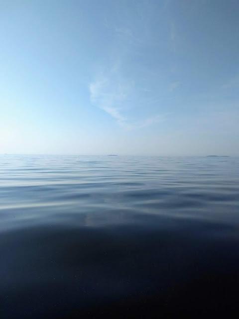 Tyyni meri, hento pilven haituva taivaalla.
