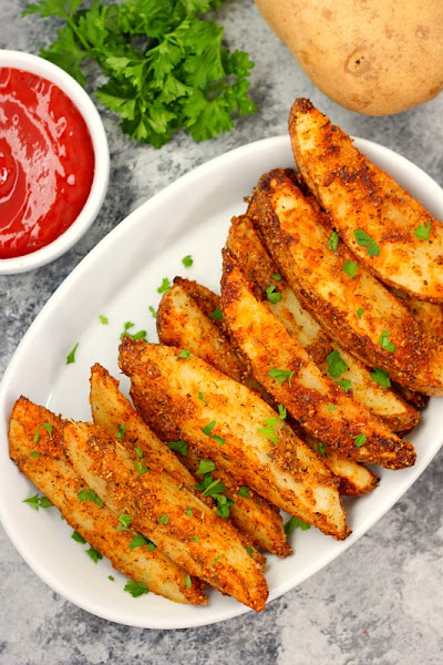 Top view of baked garlic parmesan potato wedges on a white oval plate.