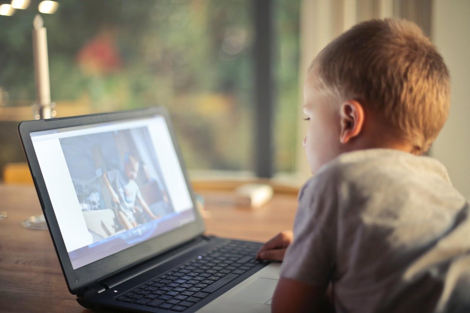 Menino assistindo desenho animado infantil no notebook