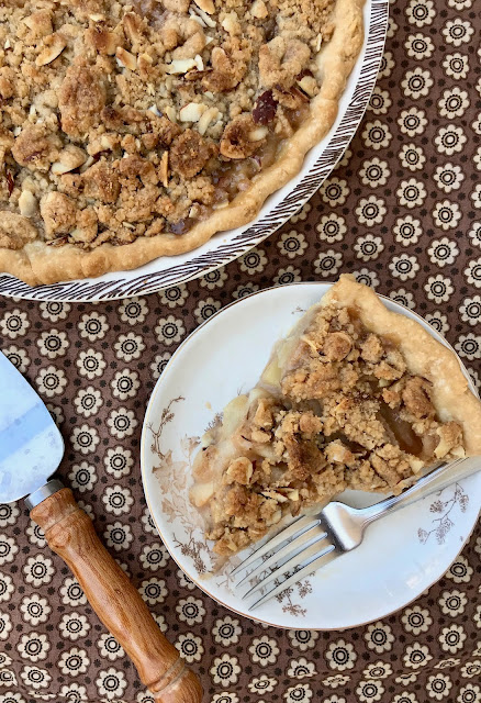 A slice of pear almond crumble pie on a small plate next to the whole pie.