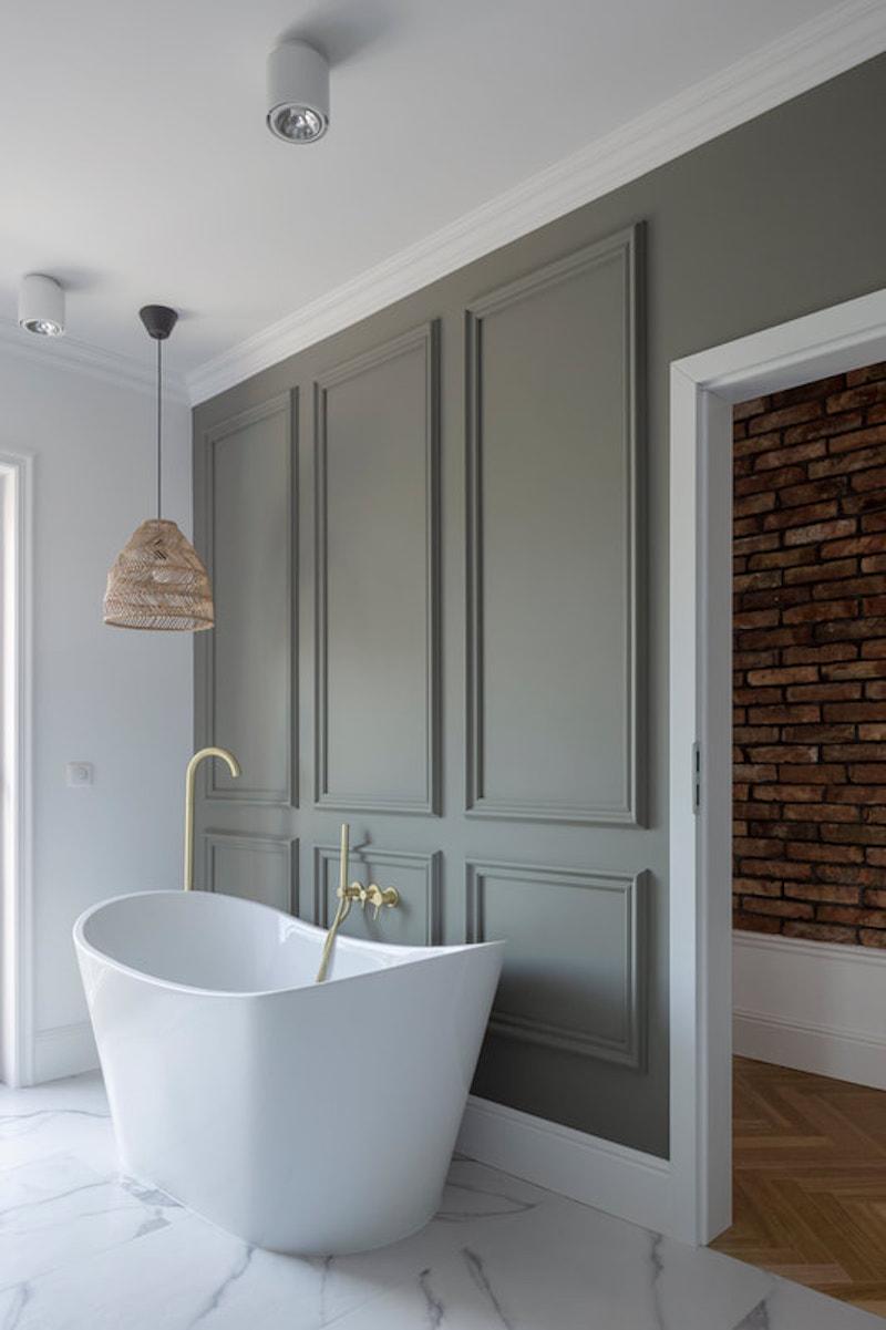 Baño clásico de suelo de mármol con bañera exenta y pared con cuarterones de escayola verde.